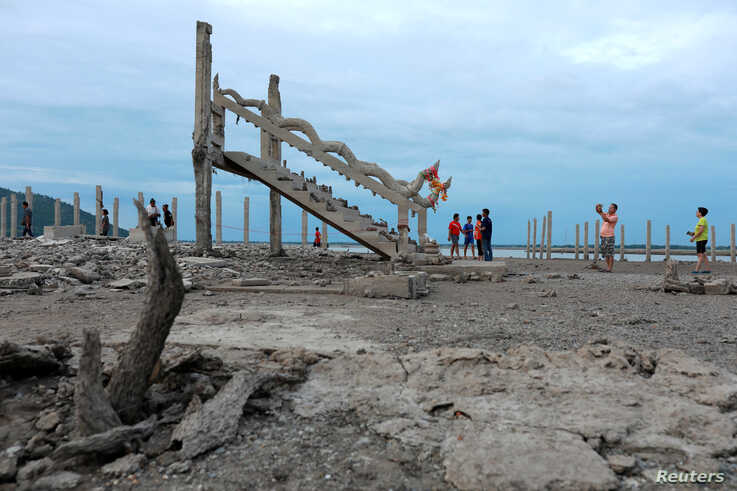 People walk and take pictures at the ruins of a Buddhist temple which has resurfaced in a dried-up dam due to drought, in Lopburi, Thailand, Aug. 1, 2019.