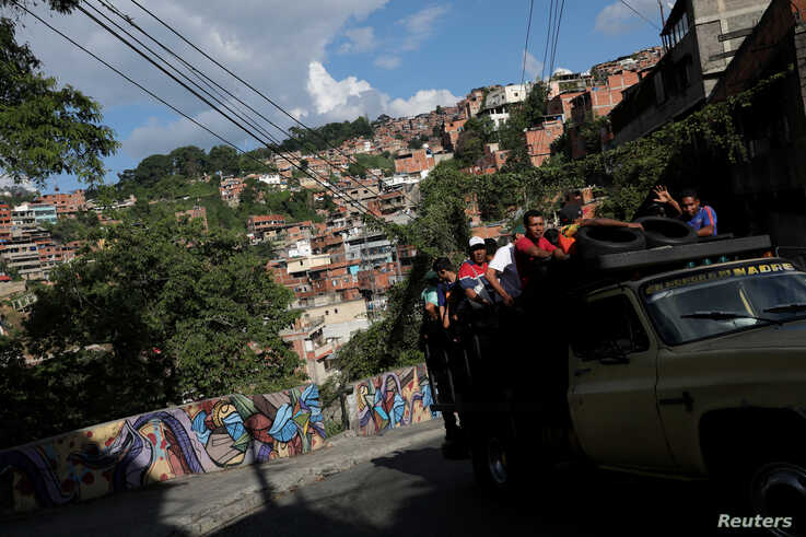 People riding in a truck drive pass by a mural in Petare slum, in Caracas, Venezuela, Aug. 7, 2019.