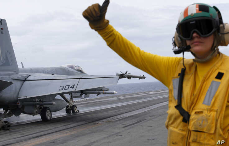 FILE - A U.S. fighter jet takes off from the U.S. aircraft carrier USS Ronald Reagan to patrol the international waters off the South China Sea, Aug. 6, 2019.
