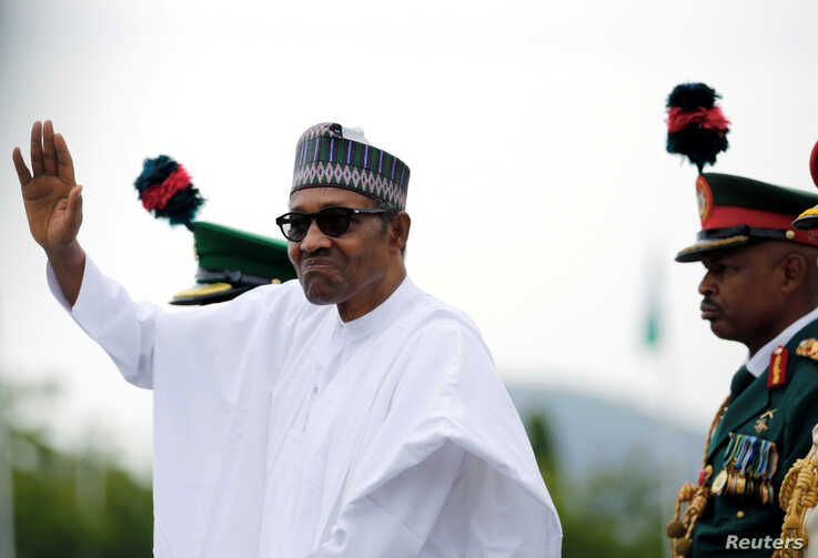 FILE - Nigerian President Muhammadu Buhari waves to the crowd while he drives around the venue during his inauguration for a second term in Abuja, Nigeria, May 29, 2019.