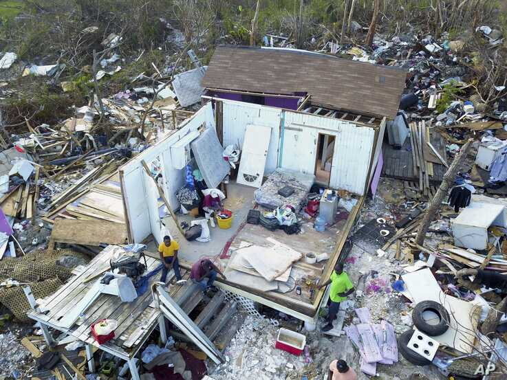 Two Haitian migrants sit as one stands amid the ruins of a home destroyed by Hurricane Dorian in Abaco, Bahamas, Sept. 28, 2019.