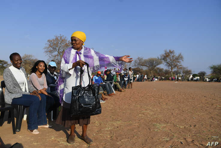 A woman talks to other voters while waiting in a queue to cast their vote at a polling station in Gaborone on October 23, 2019…