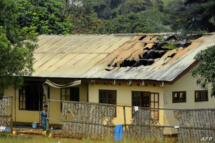 FILE - A woman stands outside a damaged school dormitory after it was set on fire in Bafut, in the northwest English-speaking region of Cameroon, Nov. 15, 2017. The military says it is helping clean up towns in efforts to implement new peace resolutions.