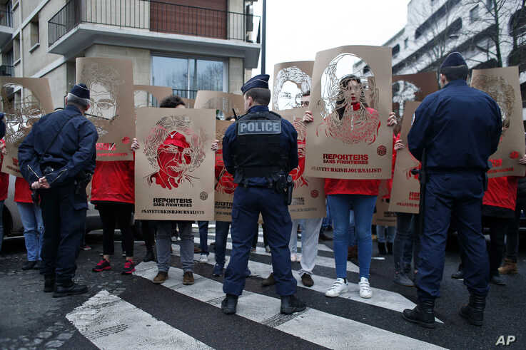 FILE - Members of Reporters Without Borders (RSF) hold stencils representing portraits of imprisoned Turkish journalists, during a…