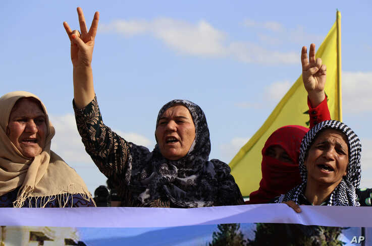 Kurdish women flash victory signs and shout slogans as they protest against possible Turkish military operation on their areas,…