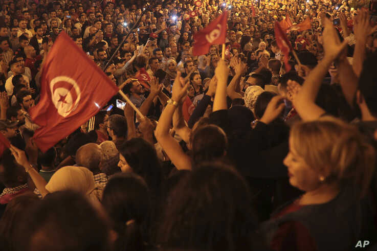 A crowd gathers on Tunis' main avenue, Oct. 13, 2019. Tunisian polling agencies are forecasting that conservative law professor Kais Saied has overwhelmingly won the North African country's presidential election.