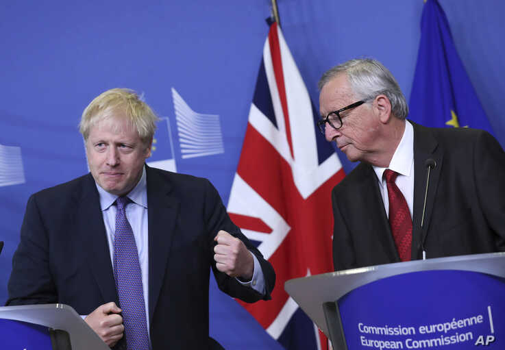 British Prime Minister Boris Johnson gestures as he stands alongside European Commission President Jean-Claude Juncker during a…