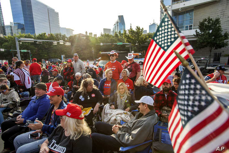 Supporters of President Donald Trump wait to enter a campaign rally as the sun rises, Oct. 17, 2019, outside the…