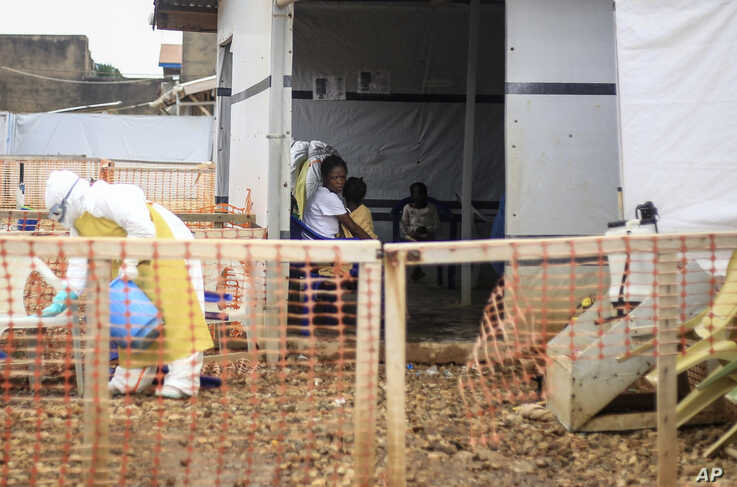 A woman whose 5-year-old daughter had a fever and was vomiting sits with her in an Ebola transit center where potential cases…