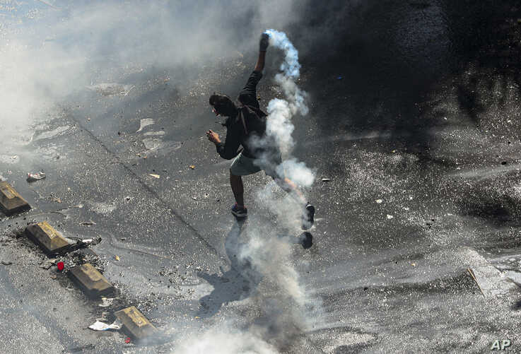 An anti-government demonstrator throws a tear gas canister back at the police during a protest in Santiago, Chile, Tuesday, Oct…