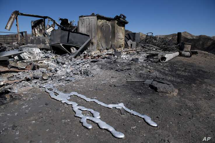 Debris from a hilltop home smolders after being burned by the Tick Fire, Oct. 25, 2019, in Santa Clarita, Calif. An estimated 50,000 people were under evacuation orders in the Santa Clarita area north of Los Angeles.