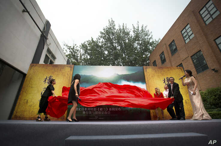 Movie executives, including Hollywood director Catherine Hardwicke, fourth from right, pull a sheet away from a poster…