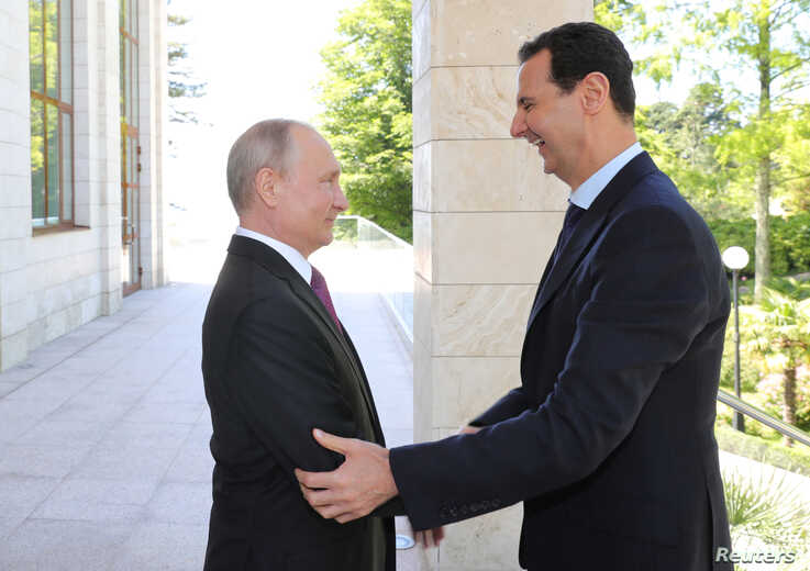 Russian President Vladimir Putin welcomes Syrian President Bashar al-Assad during their meeting in the Black Sea resort of…