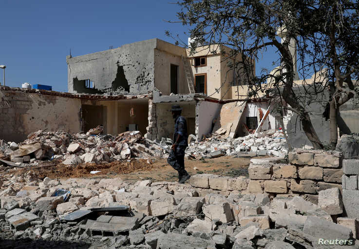 A security member inspects the site of an overnight air strike, which hit a residential district in Tripoli, Libya October 14,…