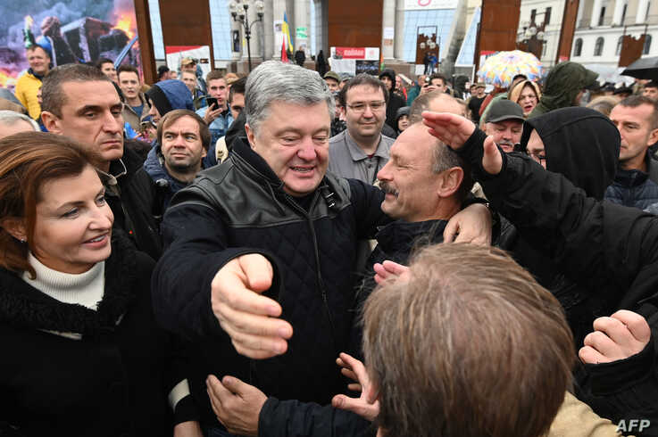 Demonstrators greet former Ukrainian President Petro Poroshenko (C) in central Kyiv Oct. 6, 2019, during a protest against broader autonomy for separatist territories, part of a plan to end a war with Russian-backed fighters.