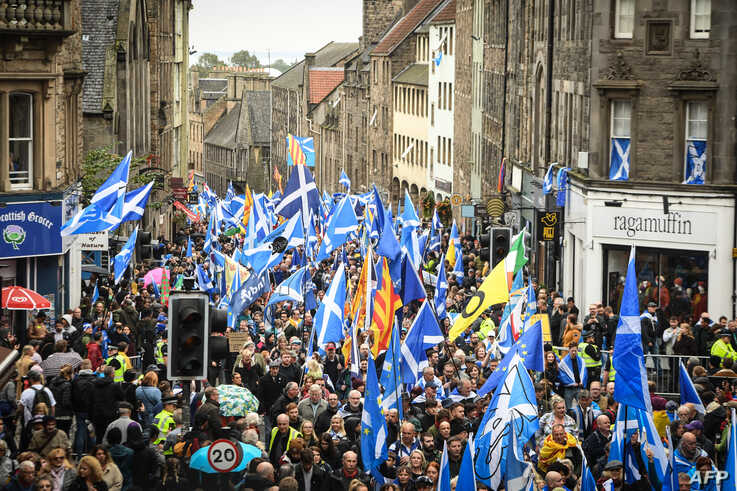 Pro-independence activists wave Scottish Saltire flags as they march in Edinburgh, Scotland, Oct. 5, 2019.
