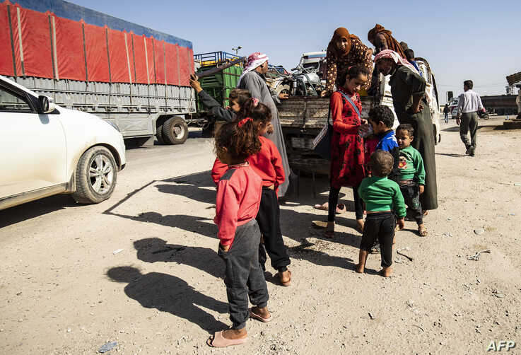 Syrian Arab and Kurdish civilians arrive to Tall Tamr town, in the Syrian northwestern Hasakeh province, after fleeing Turkish bombardment on the northeastern towns along the Turkish border, Oct. 10, 2019.