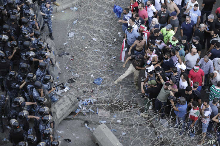 Riot police stand guard as anti-government protesters try to remove a barbed-wire barrier to advance towards the government buildings during a protest in Beirut, Lebanon, Oct. 19, 2019.