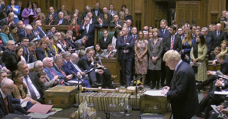 Britain's Prime Minister Boris Johnson delivers a statement to lawmakers inside a crowded House of Commons in London, Oct. 19, 2019. At a rare weekend session, Johnson implored legislators to ratify a last-minute Brexit deal he struck with EU leaders.