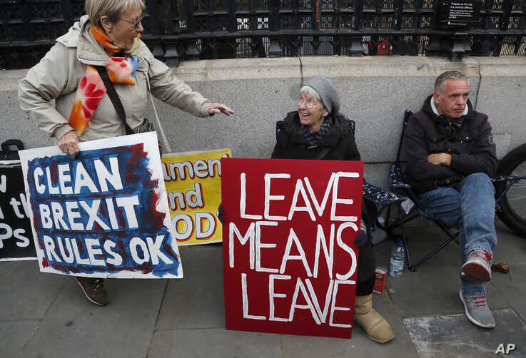 Brexit supporters display their signs in front of Parliament in London, Oct. 23, 2019.