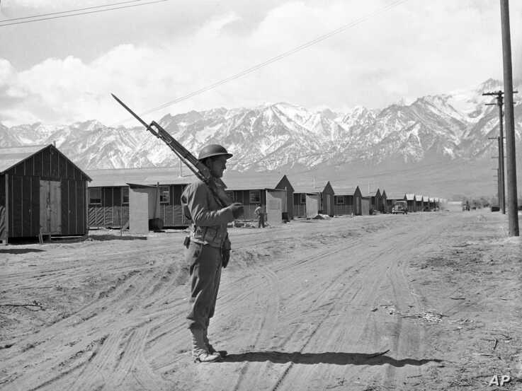 File - An American soldier guards a Japanese internment camp at Manzanar, Calif., May 23, 1943.