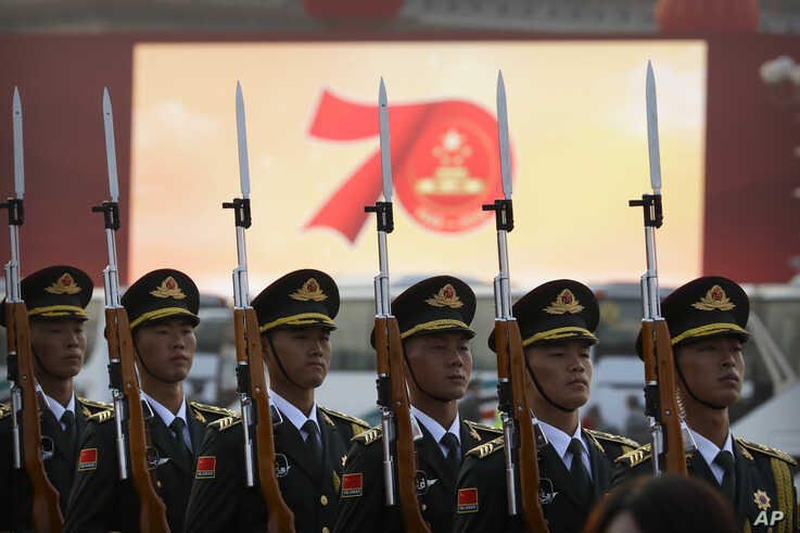 Members of a Chinese military honor guard stand at attention during a rehearsal before a parade to commemorate the 70th anniversary of the founding of Communist China, in Beijing, Oct. 1, 2019.
