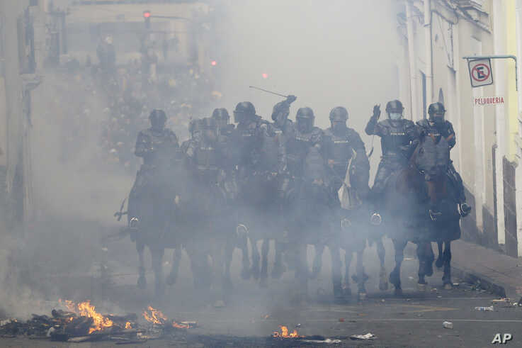 Mounted police cross a burning barricade in pursuit of anti-government demonstrators during a nationwide strike against President Lenin Moreno and his economic policies, in Quito, Ecuador, Oct. 9, 2019.