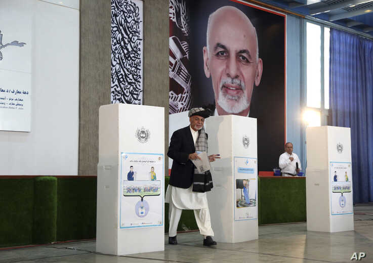FILE - Afghan President Ashraf Ghani, center, walks toward a ballot box before casting his vote at Amani High School, near the presidential palace in Kabul, Afghanistan, Sept. 28, 2019.