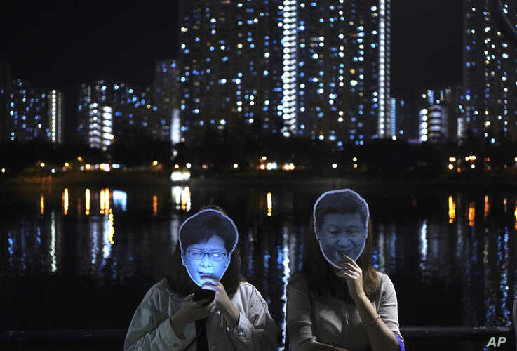Protesters wear masks of Chinese President Xi Jinping, right, and Hong Kong Chief Executive Carrie Lam during a protest in Hong Kong, Oct. 18, 2019.