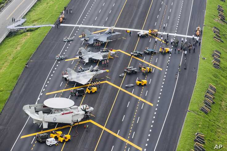 In this photo released by Military News Agency, Taiwan war planes are parked on a highway during an exercise in Changhua in southern Taiwan, May 28, 2019.