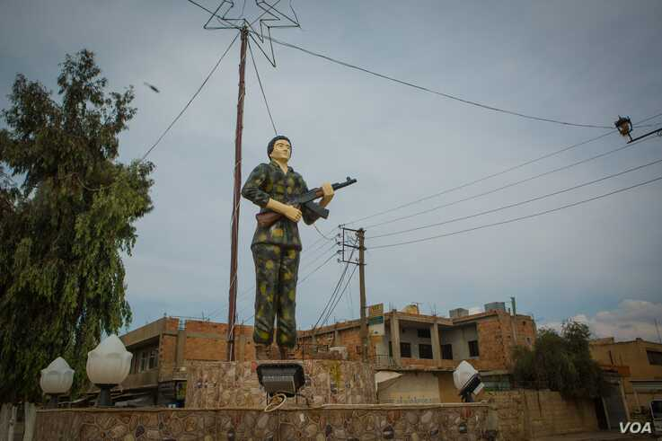 A statue of a female fighter symbolizes some of the stated goals of the Kurdish-led region: a semi-autonomous territory that expects equality, in Darbasiyah, Syria, Oct. 22, 2019. (VOA/Yan Boechat)