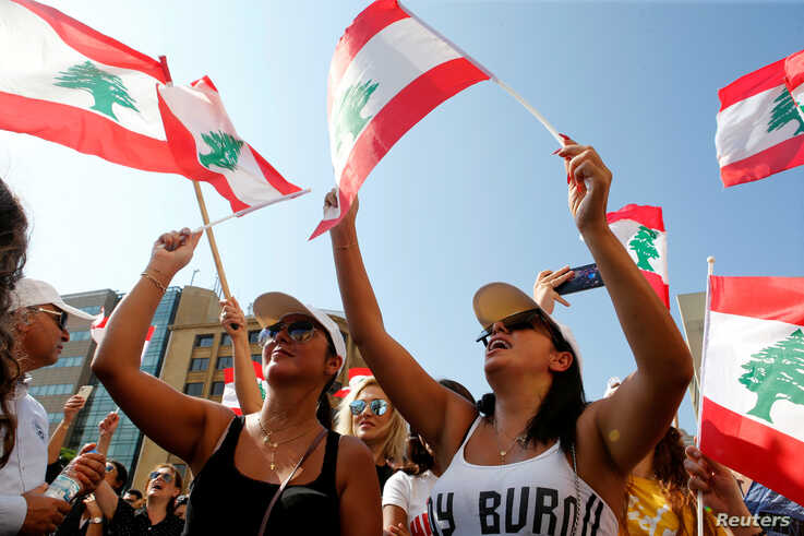 Demonstrators wave national flags during an anti-government protest in Beirut, Lebanon, Oct. 19, 2019.