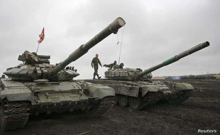 FILE - A member of the self-proclaimed Donetsk People's Republic forces walks on top of a tank during a drill outside Torez, Donetsk region, Ukraine, Sept. 14, 2015.