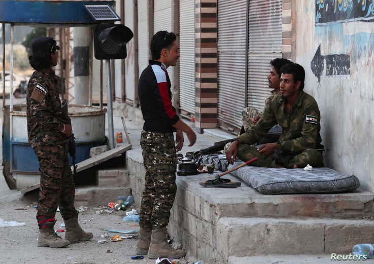 Turkey-backed Syrian rebel fighters chat in the border town of Tal Abyad, Syria, Oct. 18, 2019.