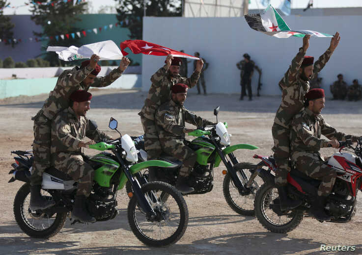 FILE - Fighters of Syrian National Army, backed by Turkey, ride on motorbikes during a graduation ceremony in the city of al-Bab, Syria, Aug. 5, 2018.