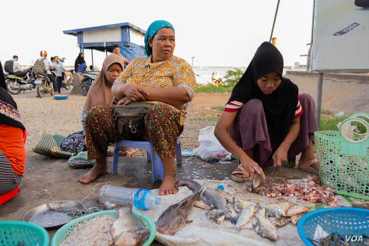 Khmer Islam fish seller Sos Nob, 48, sits beside her niece in front of the Sokha ferry entrance on the evening of Oct. 14, 2019 in Phnom Penh, Cambodia. (Malis Tum/VOA Khmer)