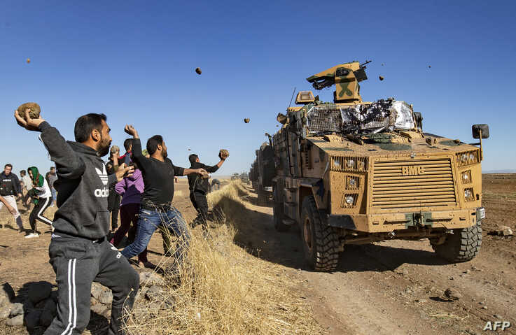Kurdish demonstrators hurl rocks at a Turkish military vehicle on November 8, 2019, during a joint Turkish-Russian patrol near…