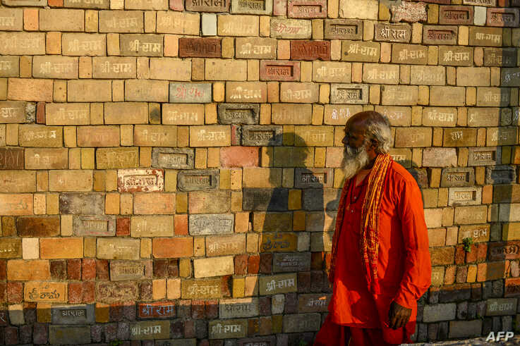 In this picture taken on November 12, 2019, a Sadhu (Hindu holy man) looks at bricks for the proposed Rama temple Ram…