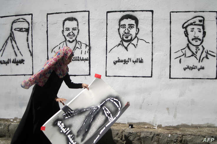 A Yemeni graffiti artist paints faces of victims of an al-Qaida militant attack on a wall during an