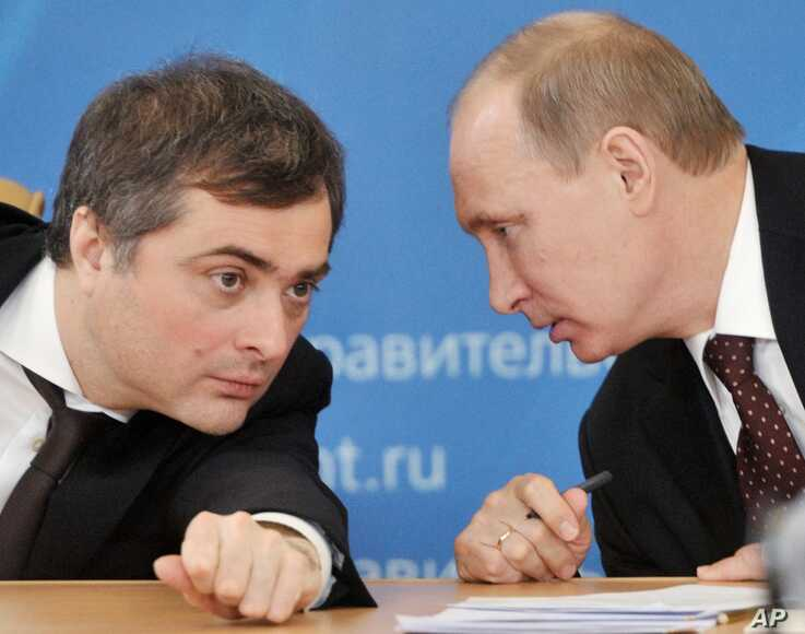 FILE - Russian Prime Minister Vladimir Putin, right, speaks to Vladislav Surkov, deputy prime minister in charge of economic modernization, during a visit in Kurgan, Russia, Feb. 13, 2012.