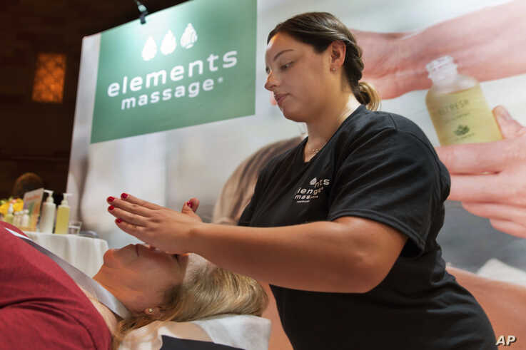 Adrianna DeJesus, right, of Elements Massage in Englewood, Colo., demonstrates their AromaRitual experience at the annual…