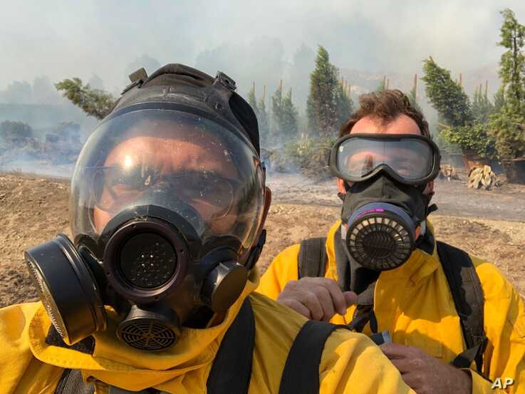 Associated Press photographer Marcio Jose Sanchez, left, takes a selfie with fellow AP photographer Gregory Bull while covering the Easy Fire on Oct. 30, 2019, in Simi Valley, California.