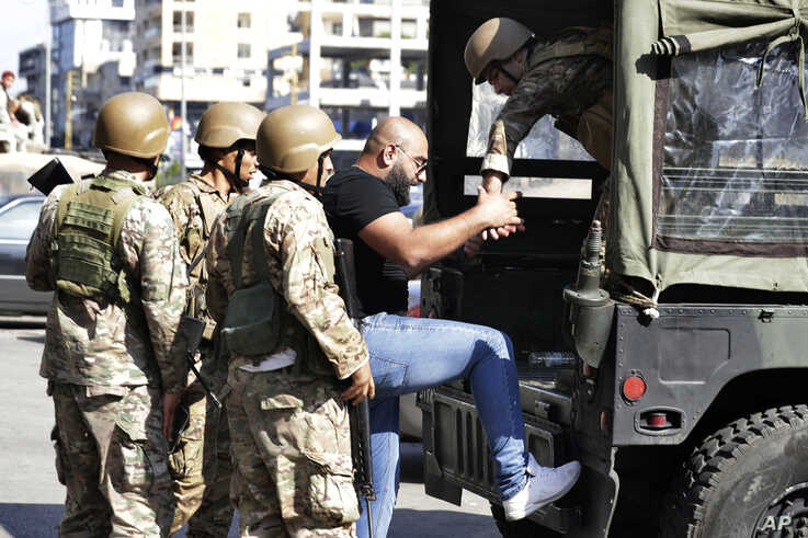 Lebanese army soldiers arrest an anti-government protester after scuffles broke out in the town of Zouk Mosbeh, north of Beirut, Lebanon, Nov. 5, 2019.