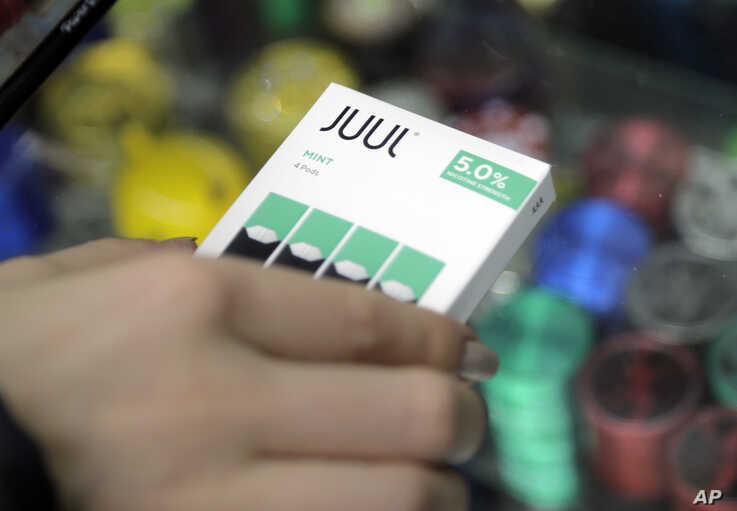 FILE - In this Dec. 20, 2018, file photo a woman buys refills for her Juul at a smoke shop in New York. The e-cigarette maker…