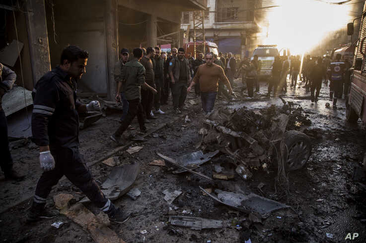 People check the aftermath of a car bomb blast in the city of Qamishli, northern Syria, Monday, Nov. 11, 2019. Three car bombs…