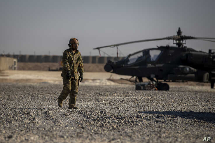 A crewman walks past an attack helicopter at a US military base at an undisclosed location in eastern Syria, Monday, Nov. 11,…