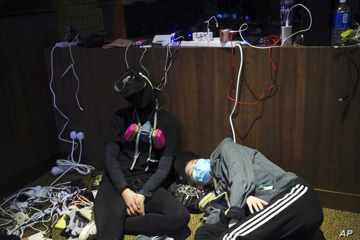 Pro-democracy protesters take a nap while charging their devices inside the campus of the Hong Kong Baptist University in Hong…