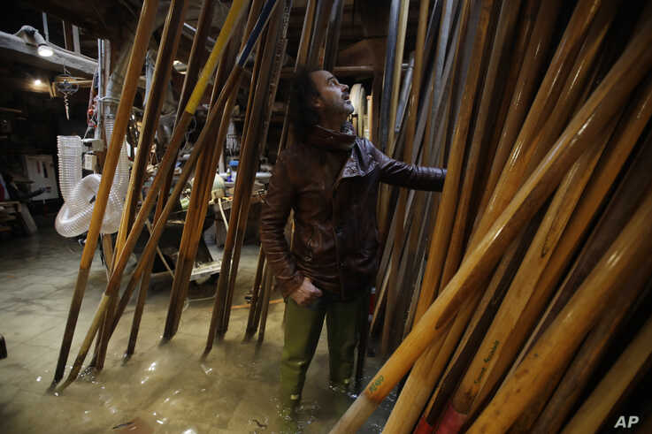 In this photo taken on Sunday, Nov. 17, 2019, Paolo Brandolisio stands in his oars flooded laboratory, in Venice, Italy…