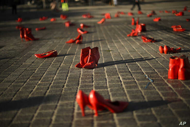 Passers-by walk past dozens of red painted shoes placed on the ground as a part of an installation against violence against…
