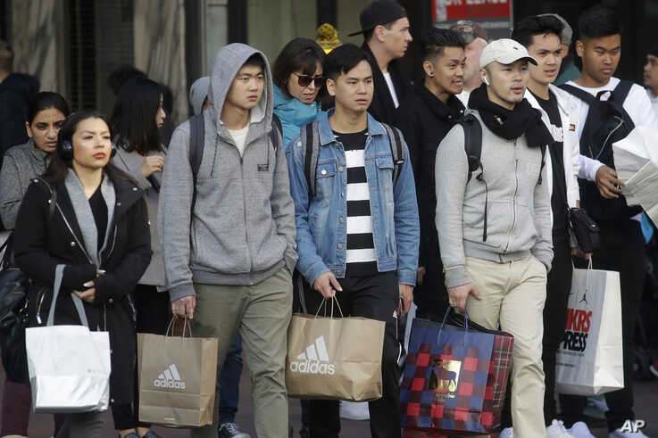 Shoppers carry bags as they cross a street in San Francisco, Nov. 29, 2019. Black Friday kicks off the start of the…